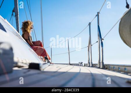 Beautiful curly adult young woman sit down on the dock of a sail boat enjoying the sun on summer holiday vacation tour - travel lady enjoying freedom and luxuryt lifestyle in outdoor leisure activity - Stock Photo