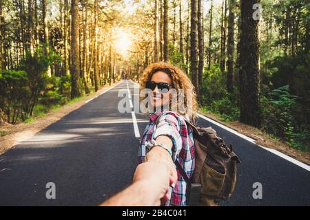 Couple travelers Man and Woman follow holding hands at long way road forest landscape and sun on background Love and Travel happy emotions Lifestyle concept. People traveling active adventure vacations