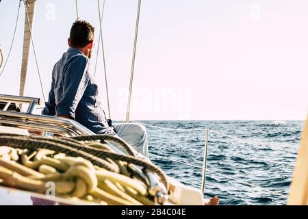 Free man enjoying outdoor leisure activity on a sail boat with blue ocean around - luxury summer holiday vacation concept - Happy people sailing with nature and nice weather - Stock Photo