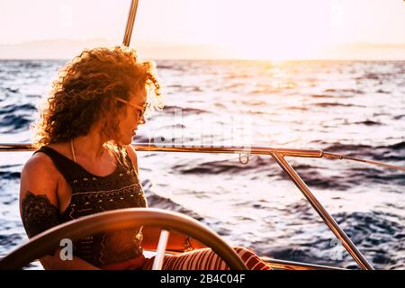 Beautiful attractive curly blonde adult woman looking the ocean enjoying a trip and travel on sail boat - modern generation people enjoy freedom and alternative lifestyle traveling - Stock Photo