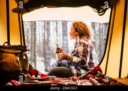 Camping with tent and adventure alternative travel vacation concept with cheerful people - beautiful adult blonde smile and enjoy the outdoors nature around in the forest sit down near a backpack and drinking coffee