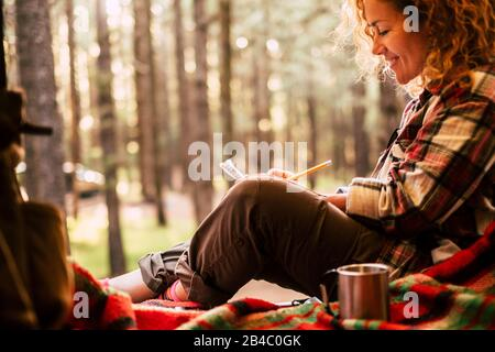 Travel alternative and wanderlust lifestyle people - beautiful young woman sit down ina tent with scenic forest outdoor in background - adventure and environment concept for free hipster female