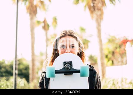 Modern cheerful beautiful blonde girl portrait with skateboard covering part of the pretty face - young millennial people outdoor concept enjoying lifestyle and sunny days - Stock Photo