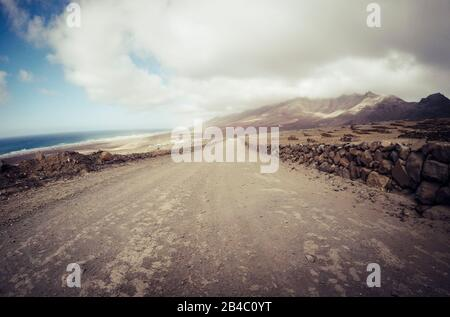 Long off road terrain way road viewed from ground level with mountains and coastline ocean view - travel and adventure concept for alternative vacation and lifestyle