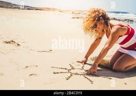 Happy cheerful woman on summer vacation enjoying the beach and the outdoor designing a sun on the sand - beautiful curly caucasian people lady in outdoor leisure activity - Stock Photo