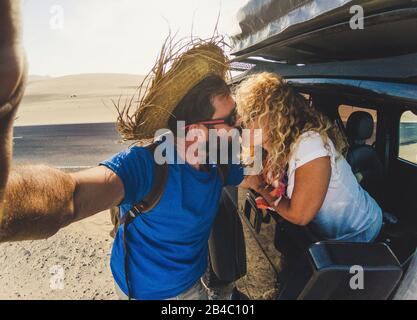 Couple of people traveler kissing and taking selfie picture - beautiful woman outside the car from window and man standing kissing her with tourist clothes - desert in background and adventure concept