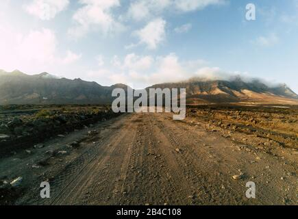 Long off road terrain way road viewed from ground level with mountains and blue cloudy sky - travel and adventure concept for alternative vacation and lifestyle