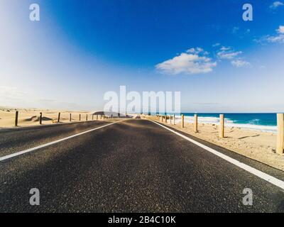Long way road for travel car transportation concept with desert and beach on the side - sea water and blue clear beautiful sky in background - motion effect