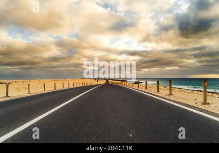 Long way road for travel car transportation concept with desert and beach on the side - sea water and cloudy beautiful sky in background - motion effect