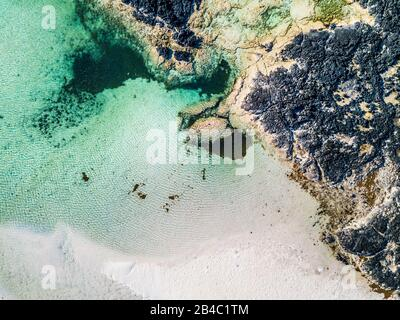 Vertical aerial view of white lagoon sand beach and clear tourquoise water - resort beautiful summer holiday destination with ocean and rocks - paradise and relax concept with nature