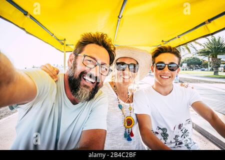 Family happy people concept - mother son and father laugh a lot and have fun together in outdoor leisure activity - caucasian group of friends different ages and generations - Stock Photo