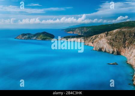 View of Assos village town and Frourio peninsular castle ruins on top. Beautiful milky blue bay with brown rocky limestone costline and moving white clouds on horizon, Kefalonia island, Greece. - Stock Photo