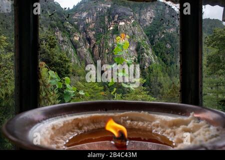 Butter lamps offered by pilgrims situated at the foot of the mountain beneath the Taktsang Goemba or Tigers nest monastery in Paro valley, Bhutan, Asi