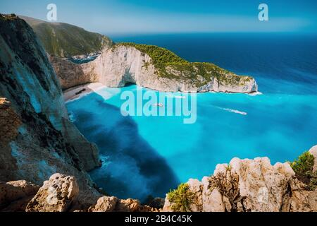 Navagio beach, Zakynthos island, Greece. Tourist boats visiting Shipwreck bay with azure water and paradise white sand beach. Famous landmark location in the world. - Stock Photo