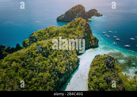 Aerial drone view of entrance to shallow tropical Big and Small Lagoon explored inside by tourist on kayaks surrounded by jagged limestone karst cliffs. El Nido, Palawan Philippines.