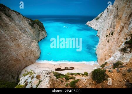 Shipwreck in Navagio beach. Azure turquoise sea water and paradise sandy beach. Famous tourist visiting landmark on Zakynthos island, Greece. - Stock Photo