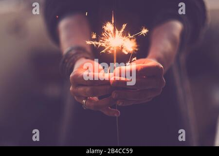 Concept of party nightlife and new year eve 2020 - close up of people hands with red fire sparklers to celebrate the night and the new start - warm colors filter - Stock Photo