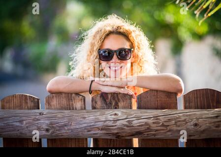 Portrait of beautiful cheerful happy woman with sun in backlight and nice smile looking at the camera - green nature background - enjoying the outdoor leisure activity in the countryside - Stock Photo