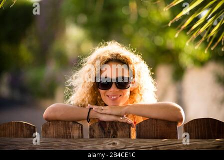 Portrait of beautiful caucasian young blonde curly woman cheerful looking at the camera with sun lights in background and defocused green natural outdoor background - happy middle age lady concept Stock Photo