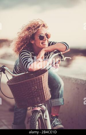 Cheerful trendy young adult caucasian woman sitting on a bike and smiling - beautiful female portrait - concept of outdoor leisure activity and happiness and joyful lifestyle Stock Photo