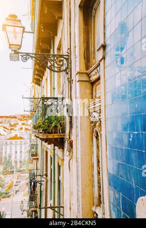 Traditional facade front of portuguese buildings with balconys and lamps. Old charming street in Lisbon, Lisboa, Lissabon, Portugal, Europe - Stock Photo