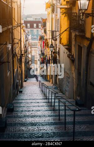 Beautiful Staircase in Lisbon. Hanging laundry in typical narrow street. Sunset in the old downtown of Lisbon, cityscape of Lissabon. - Stock Photo