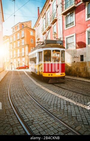 Touristic vintage red tram in a Lisbon street on sunny afternoon, narrow streets, cobblestones winding road, vacation in Lisbon - Stock Photo