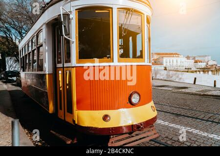 Lisbon traditional red tram on a street in Alfama district near terasse. Portugal, Europe. - Stock Photo