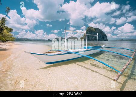 El Nido, Palawan, Philippines, Banca boat on sandy beach in shallow crystal clear water, Pinagbuyutan island in the background - Stock Photo
