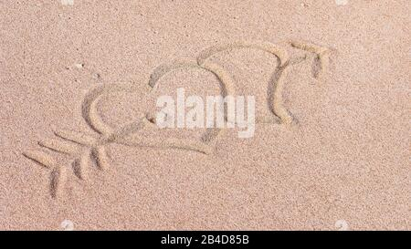 Two Hearts and arrow, We heart it, Drawn on Sand on the Beach, Bali, Indonesia. - Stock Photo