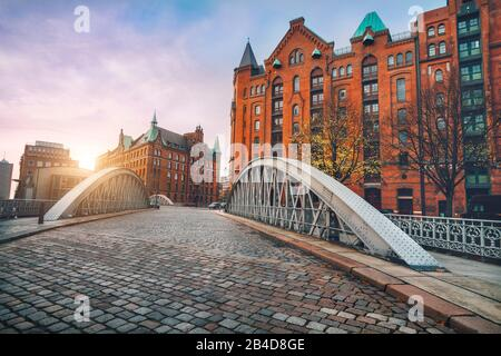 Arch bridge over Alster canals with cobbled street in historic Speicherstadt, sunset, Hamburg, Germany, Europe,
