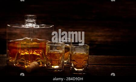 Poured whiskey from the bottle into whiskey glasses in a bar - Stock Photo