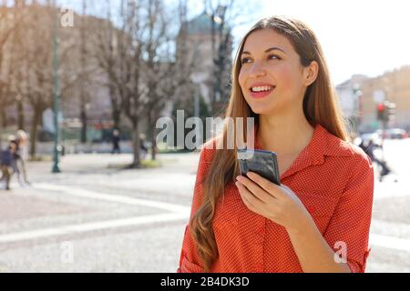 Front view portrait of a confident Brazilian woman holding mobile phone looking to the side in city street