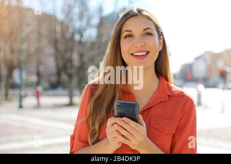 Confident casual woman holding mobile phone looking to the side in city street - Stock Photo