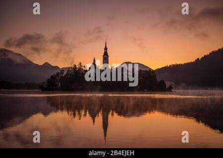 Sunrise at Lake Bled, Slovenia. Beautiful colours, early morning mist and a view over an island and a church. - Stock Photo
