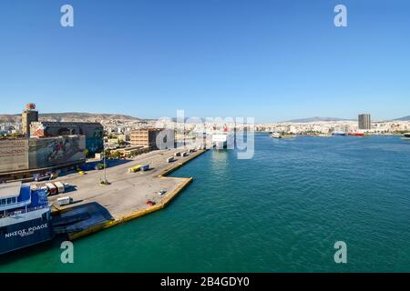 Cruise ships and ferry dock at the harbor port of Piraeus on a sunny summer day with the city of Athens Greece in view. - Stock Photo