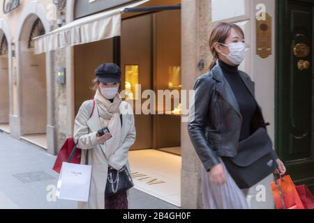 Two young Oriental women wearing surgical face masks against flu in the fashionable Via Condotti in Rome - Stock Photo