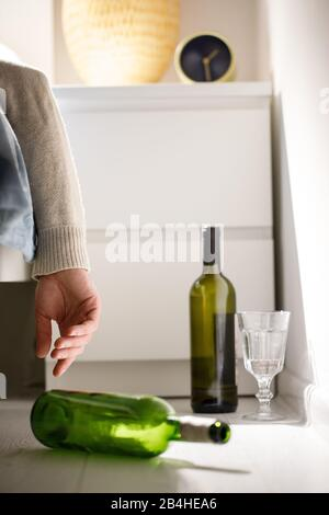 Closeup of the hand of a drunk man in clothes lying on the sofa after party, empty wine bottles on the floor. Fell asleep right in bed without undress - Stock Photo