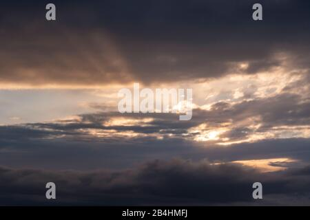 View from the window of an airplane on closed cloud cover at sunset - Stock Photo