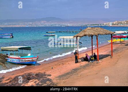 Locals at the city beach with excursion boats and view on Eilat Aqaba Aqaba, Gulf of Aqaba, Red Sea, Jordan - Stock Photo