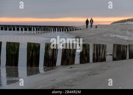 Germany, Mecklenburg-West Pomerania, Zingst, strollers on the beach, sunrise - Stock Photo