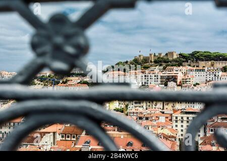 Europe, Portugal, capital city, old town of Lisbon, viewpoint, view of the ruin Castelo de Sao Jorge on the castle hill, seen through metal balustrade in the foreground - Stock Photo