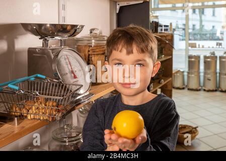 Eine Junge steht in einem Unverpacktladen an einer Waage. Er hält eine Zitrone in den Händen. - Stock Photo