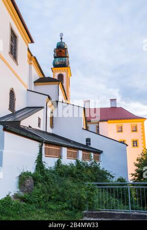 Colourful yellow bell tower on an old church or building in Passau Bavaria viewed under a cloudy sky in an urban environment