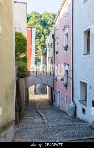 Quaint narrow cobbled lane in Passau, Bavaria, Germany in summer with arch between the buildings and view to trees