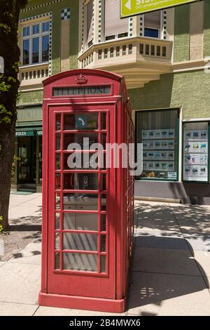 Traditional red phone booth or cabin on a street near shops in central Bad Ischl, Austria - Stock Photo