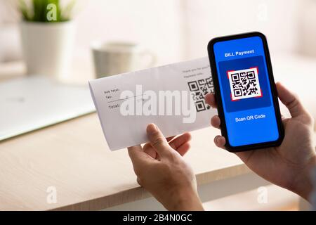Using Smartphone Scanning QR Code for bill payment option - Stock Photo