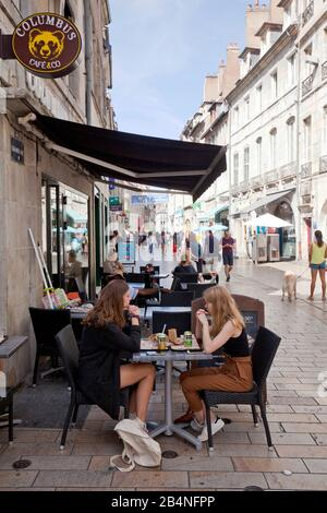Two teenagers chat in the street cafe. Street scene in the old town of Besançon. A city in the east of France. Department of Doubs. - Stock Photo