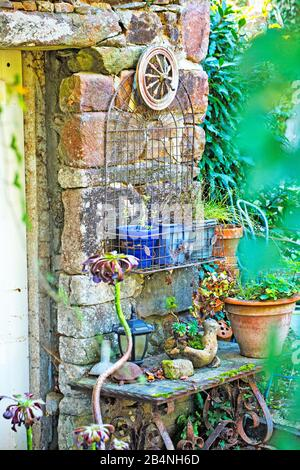 Colorful decorations on a stone house wall. In the Cote des Bruyeres region in the Finistère department. - Stock Photo