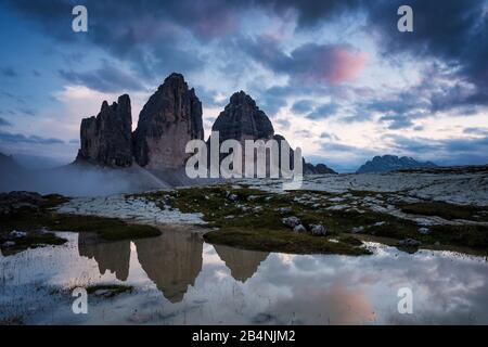 Drei Zinnen, Sesto Dolomites, South Tyrol, Italy, mountain range of the three peaks reflected in puddle after rain showers - Stock Photo